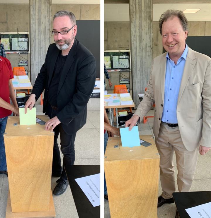 Rektor und Kanzler der Universität werfen ihren Stimmzettel in die Wahlurne.