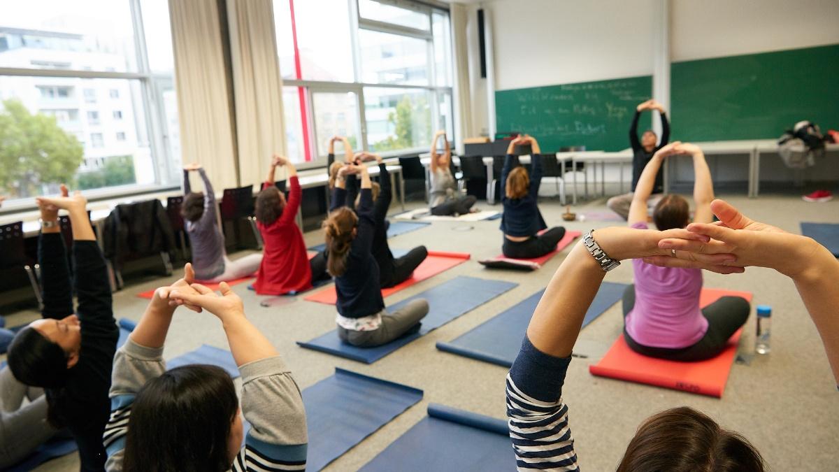 Beschäftigte der Universität Stuttgart sitzen auf Matten in einem Seminarraum und machen eine Dehnübung.  (c)