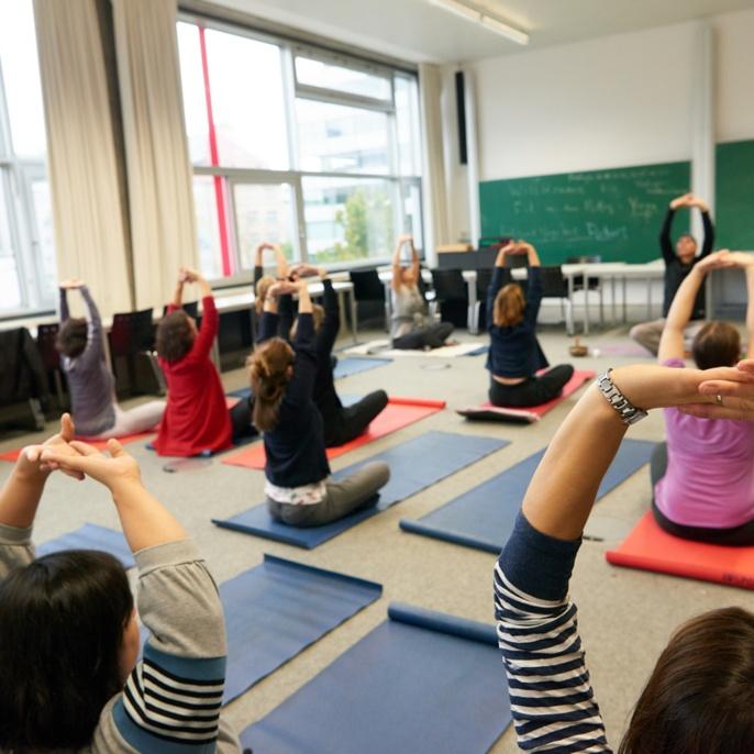 Beschäftigte der Uni Stuttgart üben auf Matten in einem Seminarraum.